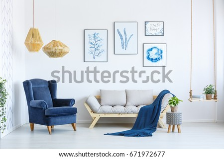 armchair living room. White sofa and blue armchair in living room with posters on the wall Sofa Blue Armchair Living Room Stock Photo 671972677