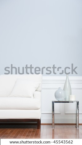 White sofa and glass end table with vases set against pale blue wall. Vertical shot. - stock photo