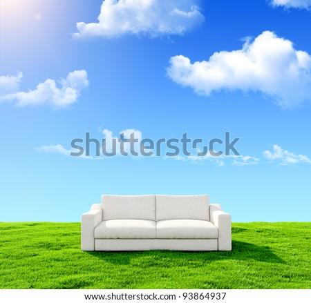 White sofa on a green field against the blue sky - stock photo