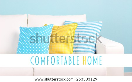 White sofa with colorful pillows on wall background, Comfortable Home concept - stock photo