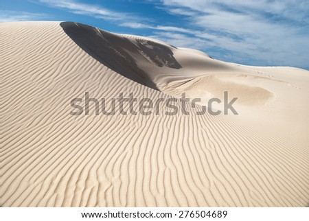 White soft big sand dune in desert with sand patterns and lines and shadows - stock photo