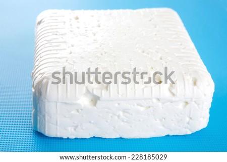 white soft feta cheese on plate over white - stock photo