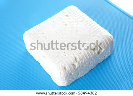 white soft feta cheese on plate over white - stock photo