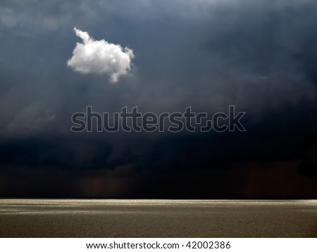 White solitary small cloud on dark sky background. - stock photo