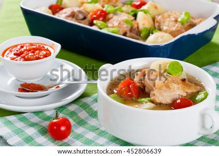 white soup bowl with stewed chicken meat, new potatoes and butter lima bean,  tomato chili sauce in gravy boat, close-up, view from above, selective focus  - stock photo