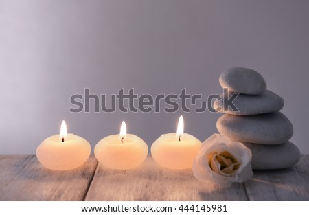 White spa stones with candles on dark background