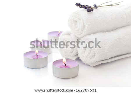 White spa towels pile with lavender and candles on white background - stock photo