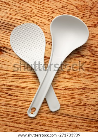 White spatula and ladle on the wooden background - stock photo