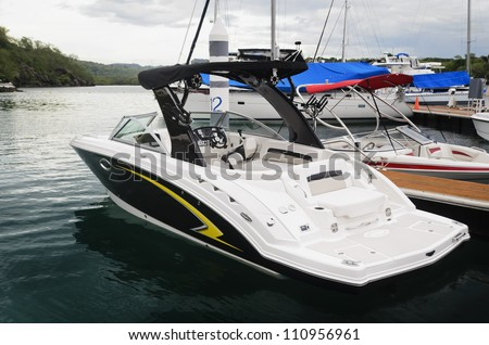 White speed boat and other sailboats anchored in a private marina, Philippines