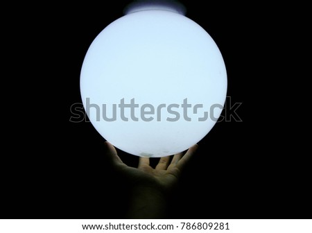 White sphere held by hand