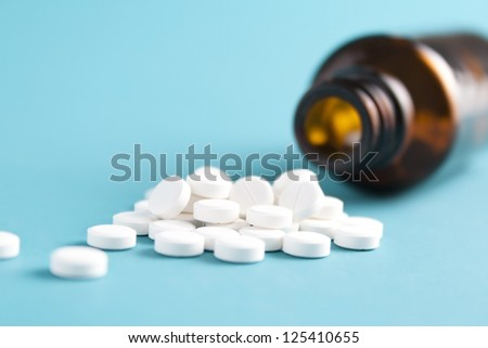 White spilled pills and bottle on blue background - stock photo
