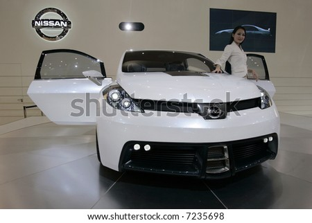 White sports car with a model at a carshow. - stock photo