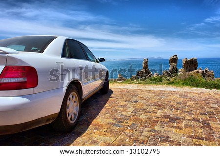 White sporty car on sea shore. Shot on Cliff Path near Hermanus, Walker Bay, Western Cape, South Africa. - stock photo