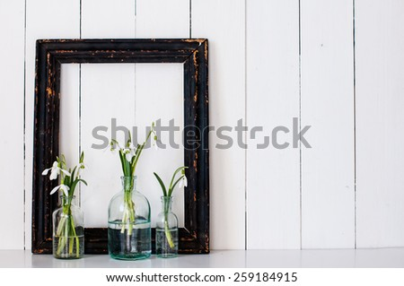 White spring flowers snowdrops in vintage glass bottles and a blck frame on an white barn wall background - stock photo