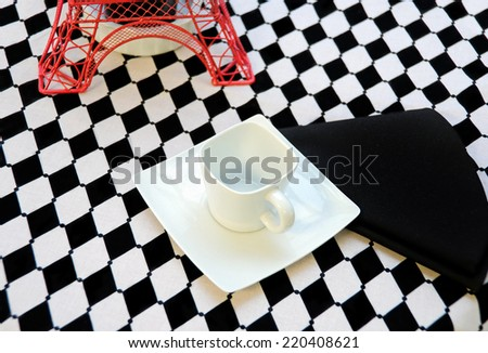 white square coffee cup on saucer with black napkin and red Eiffel tower decoration for dinner party