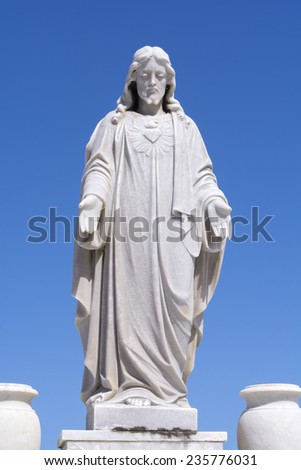 White statue of Jesus Christ standing robed with hands open looking down in cemetery with sunny clear blue sky