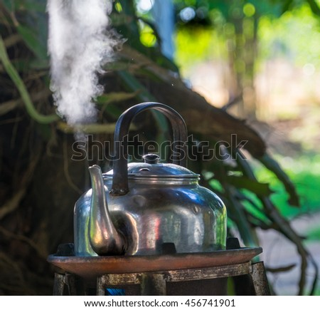 White steam from a boiling kettle outdoors, in the cool air of early morning. - stock photo