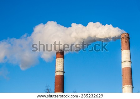 White steam rises out of a stack of a power plant  - stock photo