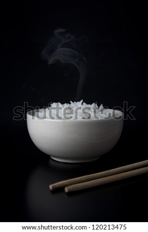 White steamed rice in white round bowl on black background