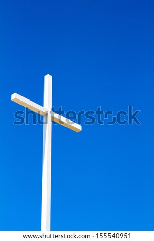 White steel fabricated Christian cross stands out against a clear blue sky.