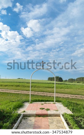 White steel semi-circular arch with an orthodox cross on it on the background of the rural landscape under a blue sky with clouds. - stock photo