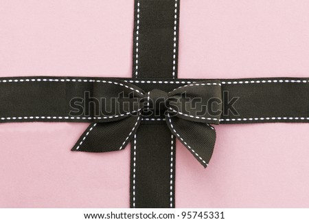 White stitched brown ribbon and bow isolated on pink background - stock photo