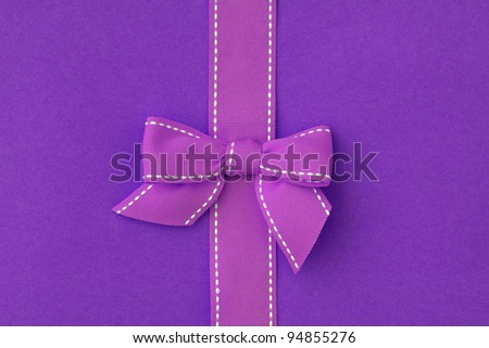White stitched pink ribbon and bow isolated on purple background - stock photo