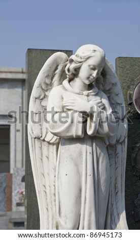 white stone angel statue in a cemetery - stock photo