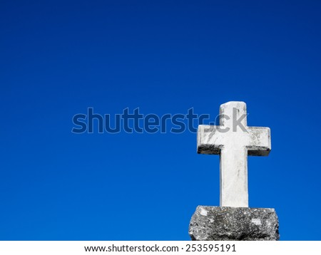 White stone cross against blue sky in New Orleans cemetery. - stock photo