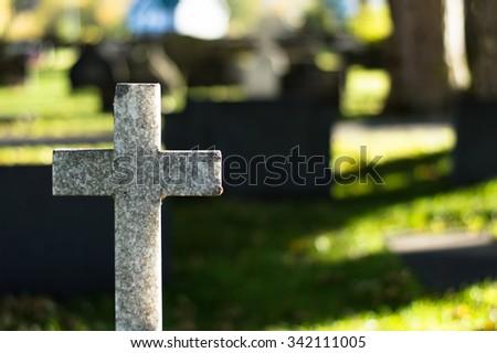 White stone cross in graveyard - stock photo