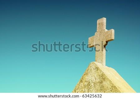 White stone cross on a beautiful blue background - stock photo