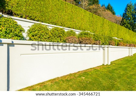 White stone fence with trimmed bush and green lawn. - stock photo