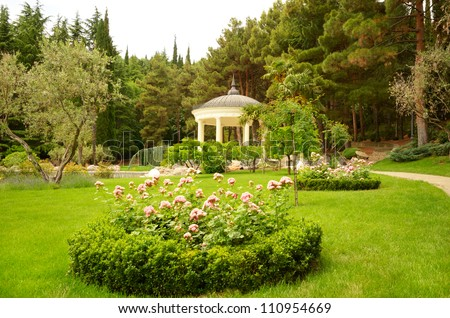 White stone gazebo in the green summer park