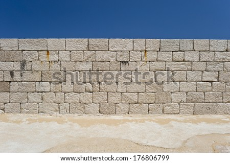 White stone wall with blue sky behind. - stock photo