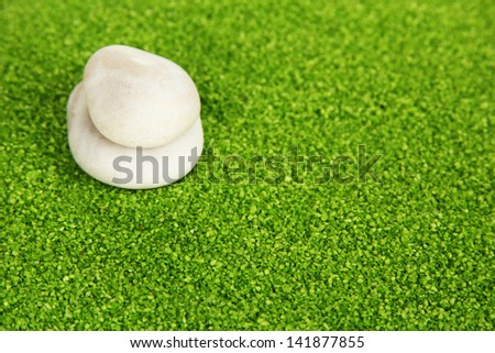 White stones on green crystals of sea salt background