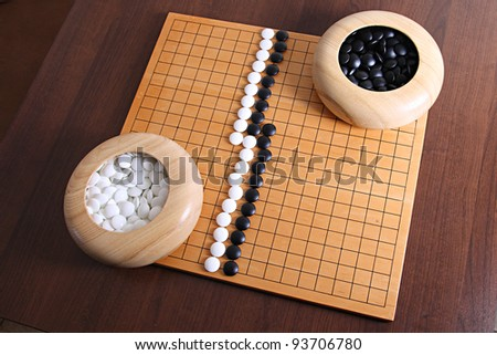 White stones winning. Top-Down View of Go Game Pieces and Board. Go is played on a grid of black lines (19×19). The playing pieces, called stones, are played on the intersections of the lines.