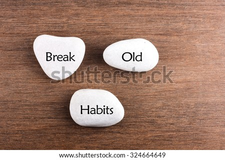 White stones with Break the old habits word on wooden background - stock photo