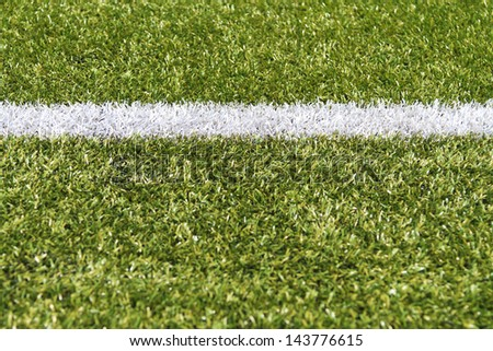White stripe on a bright green artificial grass soccer field - stock photo