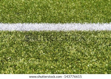 White stripe on a bright green artificial grass soccer field - stock photo