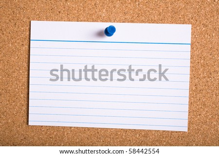 white stripped card with blue pin on cork board - stock photo