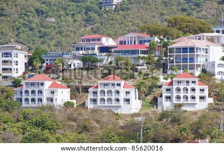 White stucco condos with red tile roofs on a tropical hillside - stock photo