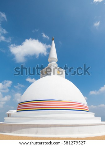 White Stupa Dagabo Wrapped With Buddhist Flag And Blue Sky Clouds At Nelligala International