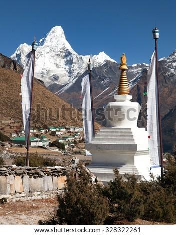 White stupa, prayer flags, mani wall with buddhist prayer symbols - mounts Kangtega, Thamserku and Ama Dablam, way to Everest base camp, Khumbu valley, Solukhumbu, Sagarmatha national park, Nepal - stock photo