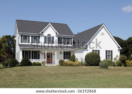 White suburban home with porch and wooden door - stock photo