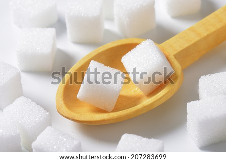 White sugar cube in a wooden scoop - stock photo