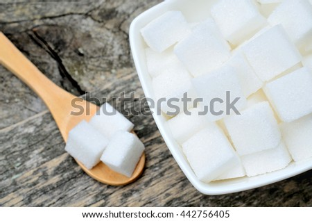 White sugar cubes in ceramic bowl on rustic table - stock photo