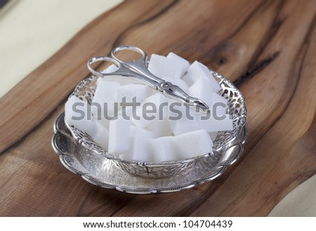 White Sugar Cubes in silver  bowl with silver tongs - stock photo