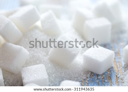 white sugar cubes on wooden surface - stock photo