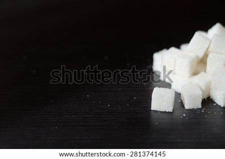 White sugar cubes piled in a heap on the black desk - stock photo