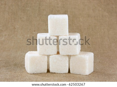 White sugar cubes pyramid on the fabric background - stock photo